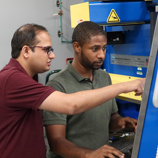 UNT post doctoral researcher Saurabu NeNe (left) and graduate research assistant Michael Frank monitor the Stir Friction Process.