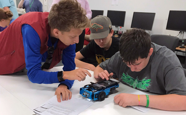Students programming a Texas Instruments Innovator Rover, a small table top robot
